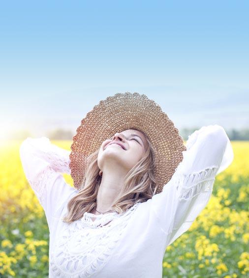 Glückliche Frau vor Blumenwiese im Sommer mit Strohhut ohne Blähungen