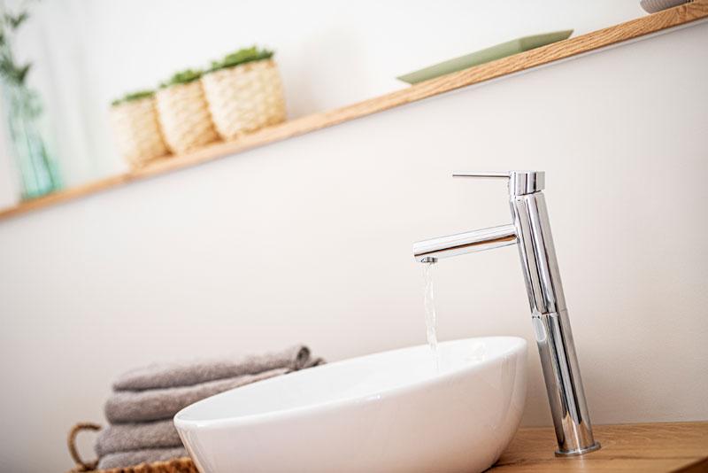 Frisches Wasser fließt aus dem Wasserhahn in Waschschüssel auf Waschtisch warme Atmosphäre