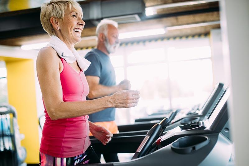Ältere Frau und älterer Mann auf Laufband aktiv und fit im Alter Erhaltung der Lebensqualität