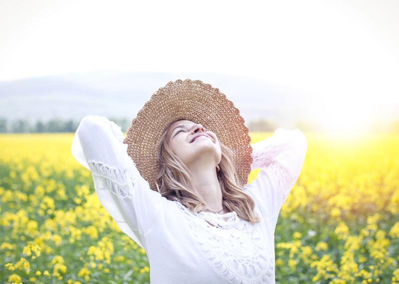 Glückliche Frau vor Blumenwiese im Sommer mit Strohhut ohne Verstopfung