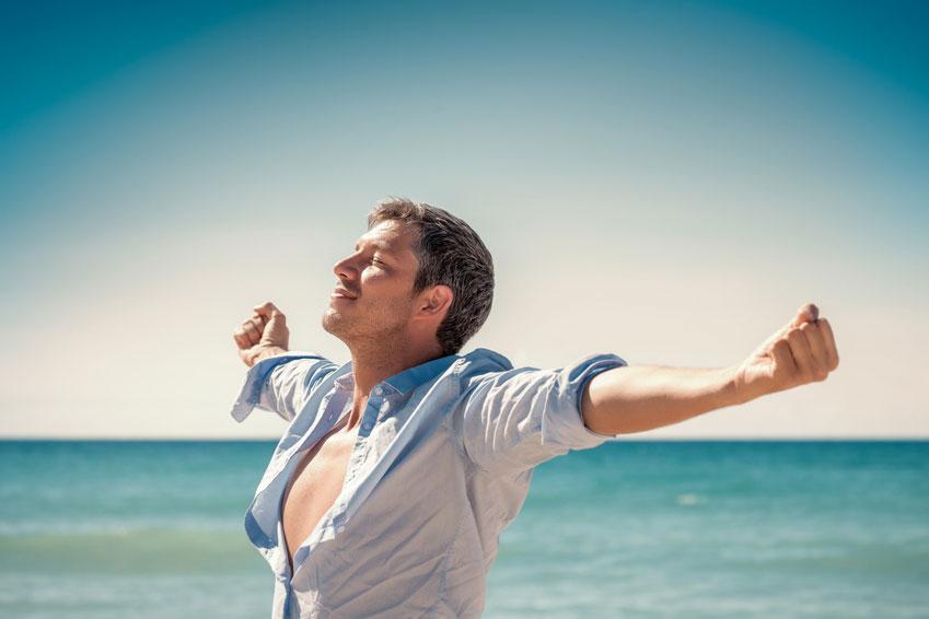 Kraftvoller energiegeladener junger Mann am Meer bei Sonnenschein atmet tief ein und genießt seine Freiheit