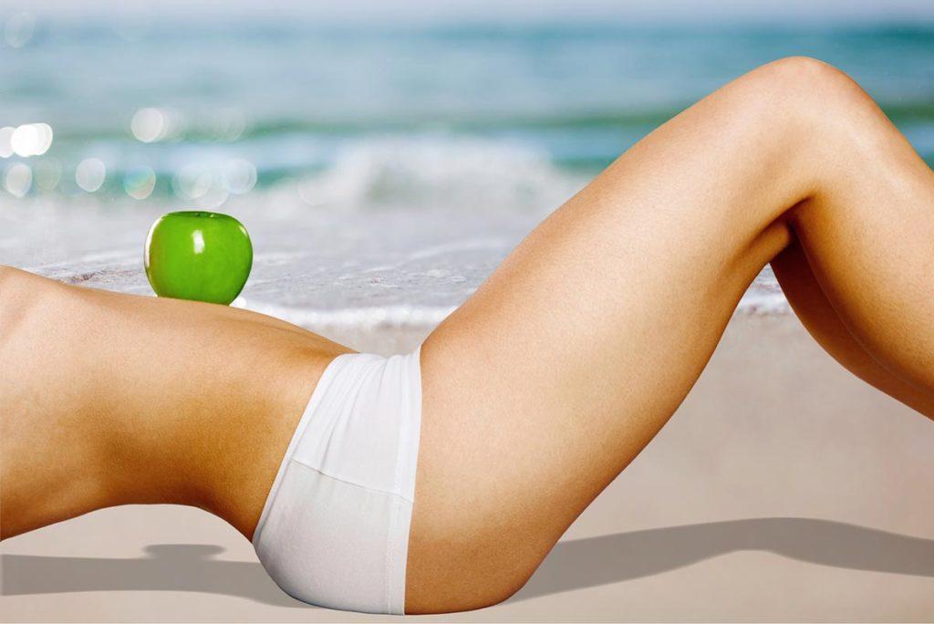 Grüner Apfel balanciert auf flachem Bauch einer attraktiven Frau am Strand Symbol für Gesundheit und Wohlbefinden