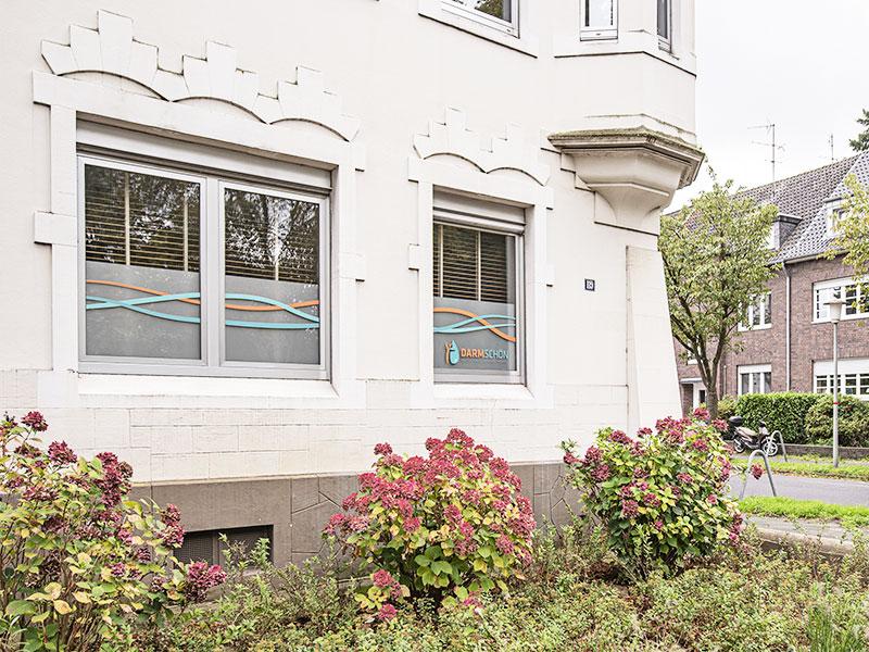 Straßenansicht des Vorgartens und Altbaus Friedrich-Ebert-Straße 119 Ecke Waldhofstraße, dem Standort des Institutes für Colon Hydro Therapie in Krefeld Bockum mit Darmschön Fensterwerbung